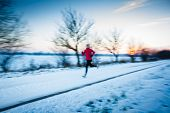 Winter running - Young woman running outdoors on a cold winter day (motion blurred image, color tone