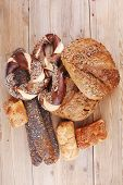 fresh rural homemade rye bread and baguette topped with sunflower seeds and sweet bagels on wooden t