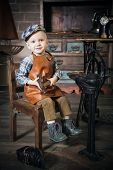 Little Boy With Hammer Imitating The Cobbler