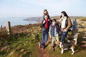 Family With Dog Walking Along Coastal Path