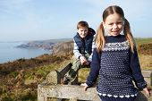 Boy And Girl Walking Along Coastal Path