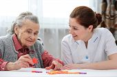 picture of geriatric  - Elder care nurse playing jigsaw puzzle with senior woman in nursing home