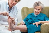 picture of chiropodist  - Nurse assists an elderly woman with chiropody and body care at home - JPG