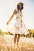 Happy pretty woman standing on the grass in floral dress on a sunny day in the countryside