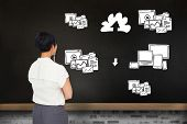 Thoughtful businesswoman against blackboard on wall with business technology doodle