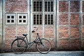 Old bike leaning against a decorative wall, Amsterdam