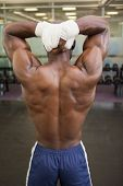 Rear view of a shirtless bodybuilder posing in gym