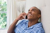 Happy man sitting on bed and talking on phone at home in the bedroom