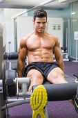 Determined young muscular man doing a leg workout at the gym