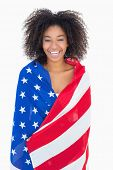 Pretty girl wrapped in american flag smiling at camera on white background