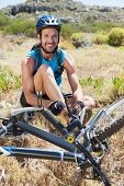 Fit cyclist tying his shoelace on mountain trail smiling at camera on a sunny day