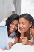 Happy mother and daughter using tablet together at home in bedroom