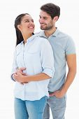 Cute couple embracing and smiling at each other on white background