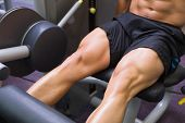 Close up mid section of muscular man doing a leg workout at the gym