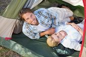 Attractive couple lying in their tent on a sunny day