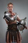Gladiator in armour posing with helmet over grey background