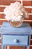Beautiful bouquet of peonies on wooden stand, on bricks background