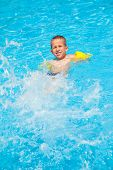 Happy boy with water rings have a fun in swimming pool