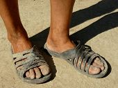 dirty male feet in rubber slippers on dried earth