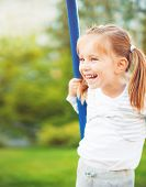 Pretty little girl on outdoor seesaw