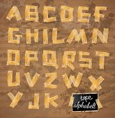 Vintage style alphabet made of yellow distressed tape with ink drops over a grunge beige background.