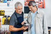 Portrait of senior salesman accepting payment through NFC technology from male customer in hardware store