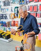 Senior man analyzing air compressor hose in hardware shop