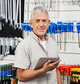 Portrait of happy senior customer holding tablet computer in hardware store