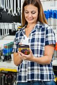 Mid adult female customer scanning product's barcode on mobilephone in hardware store