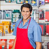 Portrait of handsome young salesman in red apron smiling at hardware shop
