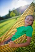 Summer joy  - lovely girl in hammock resting in the garden