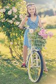 Summer Cycling - lovely girl with bicycle in rose garden