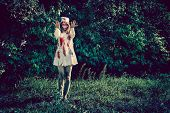 Woman zombie walking dead outdoors. Dark lighting. Color was changed to emphasize the atmosphere of