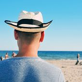 back view of a young man with a straw hat hanging out on the beach