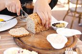 stock photo of home-made bread  - woman cut the home made bread on wooden board near tapases outside cafe - JPG