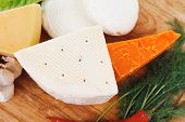 several soft and hard types of french cheese on wooden board with hot peppers and dill isolated on w