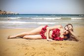 beautiful woman lying on the beach with a costume sea of flower
