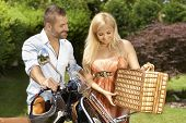Happy casual caucasian couple with scooter and picnic basket. Blonde smiling woman with handsome man