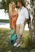 Happy romantic married couple standing in shade, outdoor. Hand in pocket, embracing, smiling.