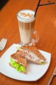 Sandwich with cheese and salmon and vegetables with latte