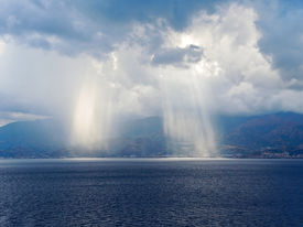 picture of messina  - light of sun come through clouds near coastline of Calabria Italy coastline inStrait of Messina - JPG