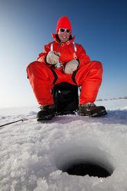 image of ice fishing  - Happy fisherman fighting a fish while ice fishing - JPG