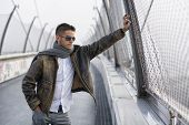 stock photo of down jacket  - Handsome trendy young man standing on a sidewalk wearing a fashionable jacket and scarf in a relaxed confident pose looking away down the bridge - JPG