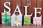 Sale with gifts on wooden background
