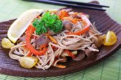 Chinese noodles with vegetables and roasted meat on plate on bamboo mat background