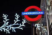 LONDON, UK - DECEMBER 20: Nighttime shot of London underground entrance sign with Christmas lights in the background. December 20, 2014 in London.