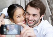 foto of two women taking cell phone  - Close up portrait of a happy young couple taking a selfie and smiling - JPG