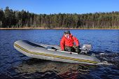 Fisherman Controls Gray Inflatable Rubber Boat With An Outboard Motor.