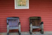 Two heavy wood chairs on front porch