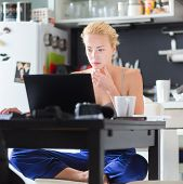 pic of morning  - Female freelancer in her casual home clothing working remotly from her dining table in the morning - JPG